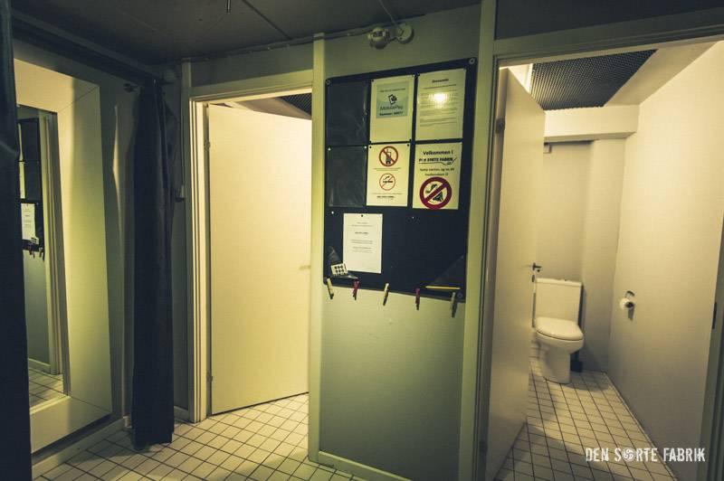 Mellemgangen med blik ind til de to toiletter i Den Sorte Fabrik
