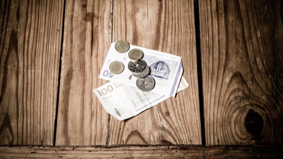 Pengesedler og mønter på træbord